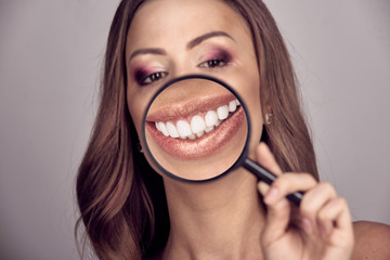 Pretty woman showing white teeth through magnifying glass