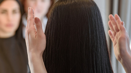 Female barber showing woman her new hairstyle