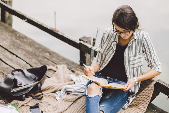 High angle view of woman reading book while sitting on pier against lake in forest