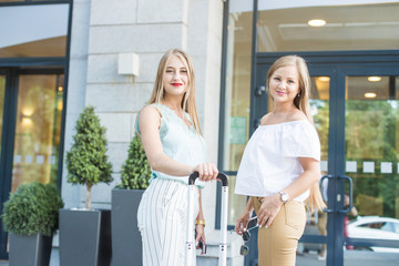 two beautiful blondes young girls with suitcases on the background of an expensive hotel. Friends of a tourist on vacation with luggage