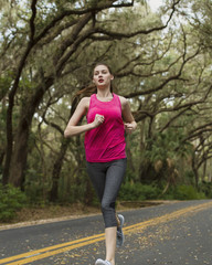 Confident woman jogging on road amidst trees in forest