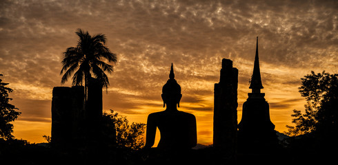 Silhouette of a Buddha statue and a temple at sunset in Thailand.