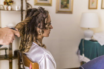 Cropped hands of hairdresser using curlers on bride's hair at home