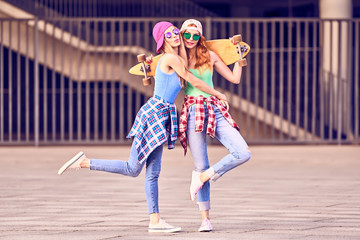Wall Mural - Two Girl in Sunglasses Having Fun with Skateboard. Outdoor, Urban background. Cheerful Friend Enjoy Summer day. Young Beautiful Model Woman Smiling in Fashion Trendy plaid shirt