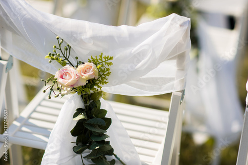 Close Up Of Wedding Flower Decoration On Chairs For Guests