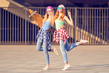 Wall Mural - Two female Skaters Fooling Around. Outdoor Urban. Playful Hipster Friend Having Fun with skateboard. Young european Woman in Fashion Trendy plaid shirt, Sunglasses