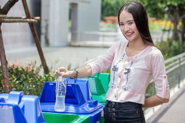 smiling asian woman throwing plastic water bottle in recycle green garbage bin