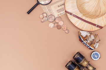 top view on items for travel, recreation and adventure: map, binoculars, straw hat, vintage paper and coins, magnifying glass, watch, compass, ship on beige background as a frame. flat lay
