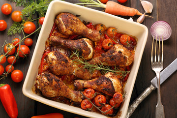 Roasted chicken legs on the ceramic bowl cooked with vegetables