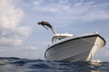 Low angle view of man diving into sea from yacht against cloudy sky
