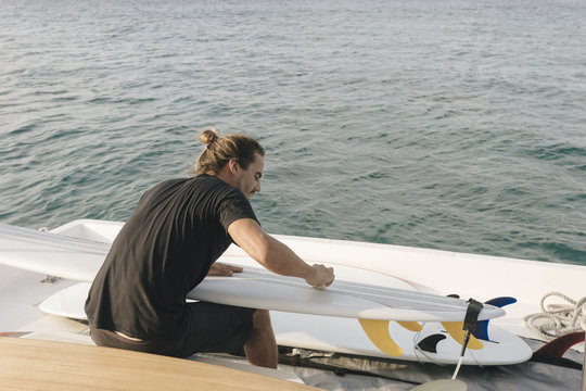 Rear view of a man cleaning surfboard while sitting in yacht