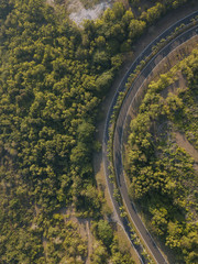 Aerial view of road amidst trees during sunny day