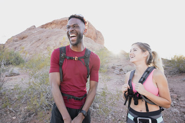 Happy friends with backpacks laughing while standing against rock formations