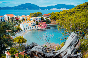 Assos village in Kefalonia, Greece. Calm blue bay water and colored traditional houses. Old snag in the front Fototapete