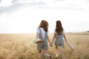 Rear view of happy twin sisters holding hands while walking on grassy field against sky during sunset