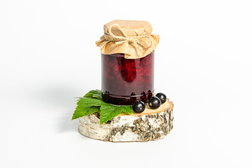 Jar with jam of berries of black currant wrapped in wrapping paper, stands on a birch stump on white background