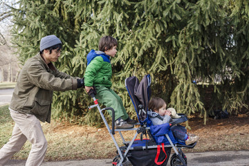 Father pushing children sitting on baby stroller in park
