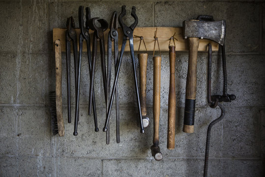 Close up of work tools hanging on a rack in the workshop