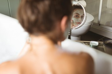 Woman applying face mask while taking bath