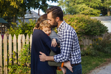 Side view of parents embracing and kissing son while standing against plants in yard