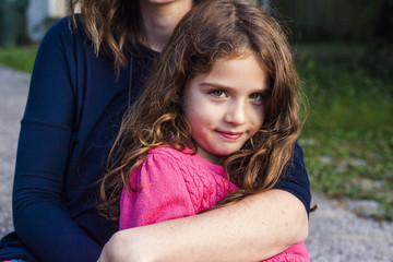 Midsection of mother embracing daughter while sitting in yard