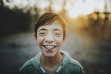 Close-up portrait of happy teenage boy standing outdoors during sunset