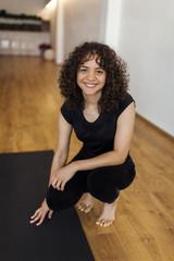 Portrait of smiling woman crouching on hardwood floor in yoga studio