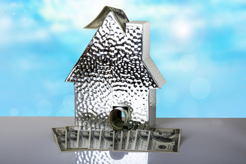 A metallic house with one hundred dollar bills on table with bright blue background. Space for text display montage. Concept of money and earnings.