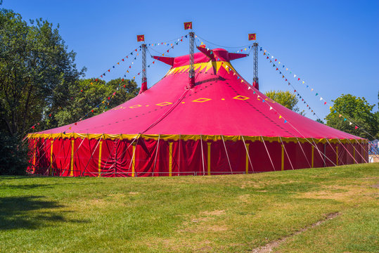 Circus tent on a green field. Red circus tent in green built in a green field against a blue sky.