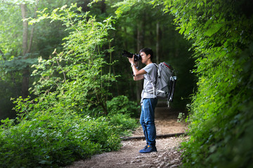 young asian smart backpacker photographer or hotography trek with backpack and camera for take a photo, picture, at Hallstatt, Austria, Europe