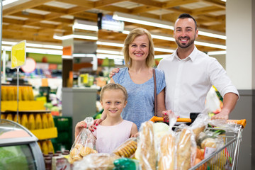Happy family standing with full cart in supermarket