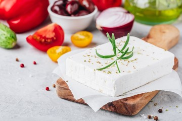 Homemade greek cheese feta with rosemary on wooden cutting board. Ingredients for greek salad