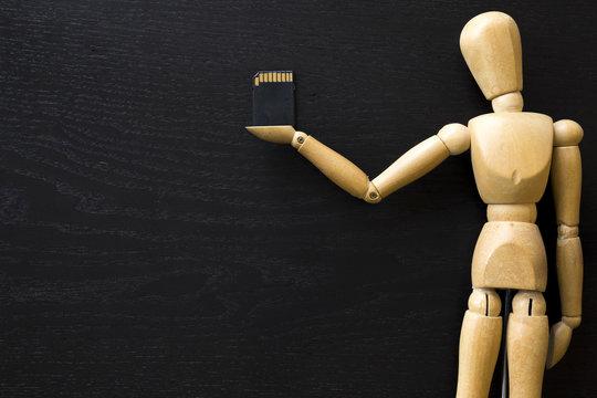 Figura de madera Maniquí Artista humano Dibujar muñeco de madera sujetando una tarjeta de memoria