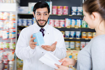 Male specialist is helping female client choose medicine in pharmacy.
