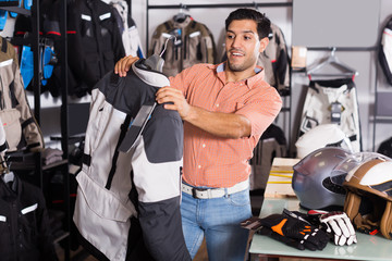 Glad man is choosing new jacket for motorbike