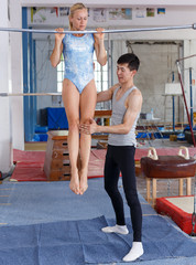 Man and woman doing acrobatic exercises in gym