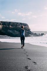 Lonely barefoot woman walking on ocean beach