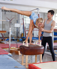 Woman in bodysuit exercising action at vaulting hourse in gym,  man helping