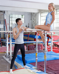 Man coaching woman doing exercises on bars