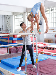 Man securing woman on bars