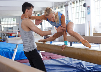 Woman in bodysuit training at broad bars in sport gym, man helping