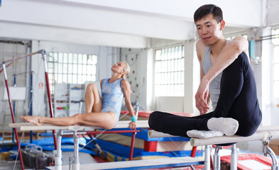 Couple  sitting on parallel bars