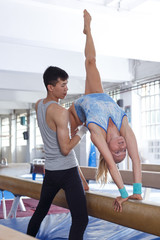 Female gymnast in bodysuit during workout at broad bars  and man helping