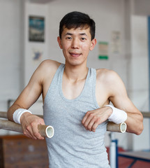 Smiling young male asian acrobat posing  at sport gym indoor