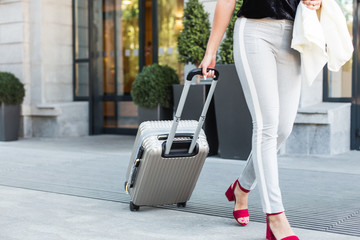 a girl in a business suit and glasses with a suitcase on the background of an expensive hotel. young beautiful woman eset luggage