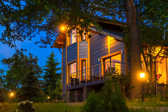 Evening. Private house with illumination. Accommodation in the Cottage. Summer evening. Cottage in the background of the evening sky. Living in the country.
