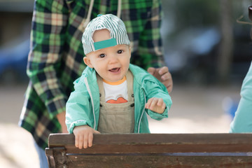 cute baby boy in a cap and jacket. outdoor portrait