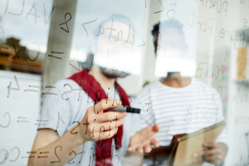 One of programmers pointing at software codes on board during discussion with colleague