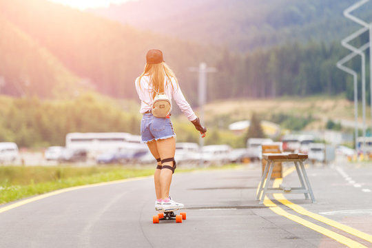Young girl with protective pads longboarding on hillside road