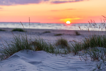 Sandy beach with sunset on background